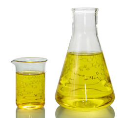 A chemical flask, a beaker with yellow liquids and a sheet of paper with formulas isolated on white background.