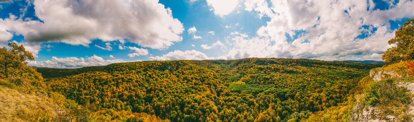 autumn landscape. top view of the yellowing leaves of the trees in the forest and blue cloudy sky on a warm Sunny autumn day