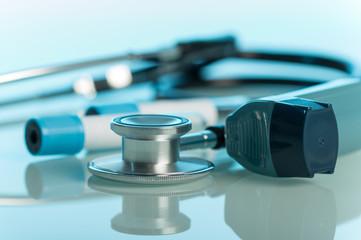 Small pocket inhaler, phonendoscope and test tubes on blue background