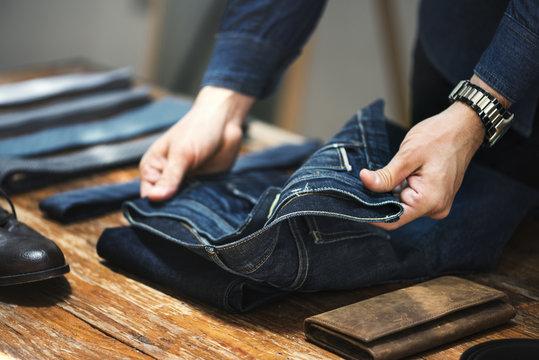 Man folding jeans