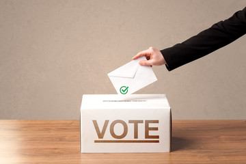 Close up of male hand putting vote into a ballot box