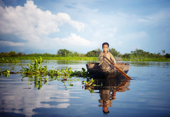 Cambodian boy traveling by boat in his floating village.