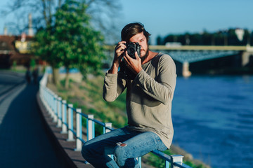 Young hipster man photographer is making landscape photography with retro old film camera medium format