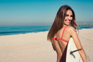 young woman carrying a surfboard at the beach.