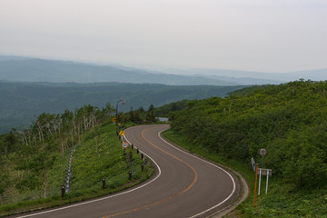 Scenic road bending through the landscapes of Akan National Park, Hokkaido, Japan