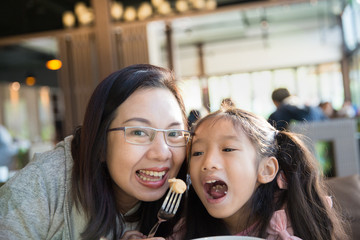 Asian family mother and daughter enjoy eating together in restaurant