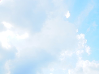 Light blue pastel sky with grey big fluffy clouds and gradient background