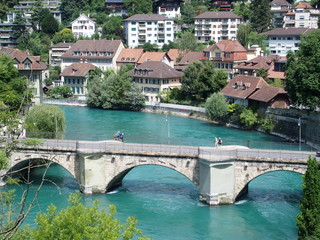 Stony bridge over clean alpine Aare river in city of Bern