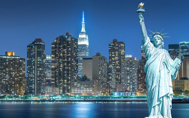 The Statue of Liberty with cityscape in Manhattan at night, New York City, USA