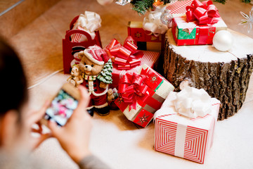 Woman taking picture of Christmas presents for sending family, focus on presents.
