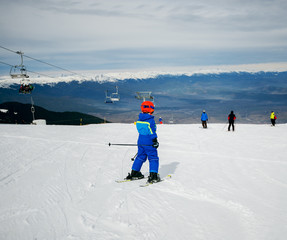 Rear view of little kid skiing in mountains with safety equipment.