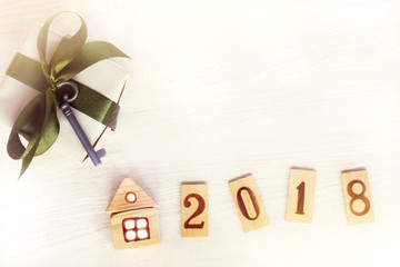 its own property in 2018/ Gift with green ribbon and a small key near layout of the house and the wooden numbers top view
