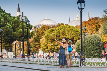 Two happy girls enjoy the breathtaking views of the sights of Istanbul. Concept of friends travel and students in Turkey