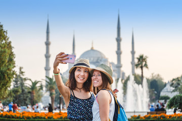 Two smiling girlfriends with smart phone doing selfie in front of the Blue Mosque in Istanbul. Travel and vacation in Turkey concept