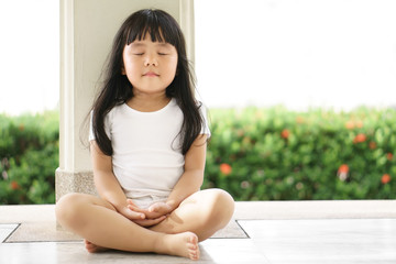 Asian children cute or kid girl sit for meditation with peace and relax in garden pavilion at temple or church and wearing white dress with sunlight on white with space Wall mural