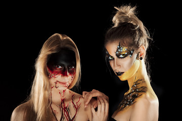 Two girls with mystic makeup. Halloween horror ladies.