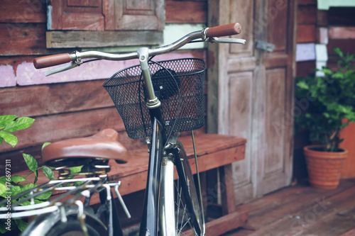 64bb161ee89 blue vintage old black and brown bicycle or bike at front of retro wooden  home terrace with wood door and window between tree in the flowerpot for  exterior ...