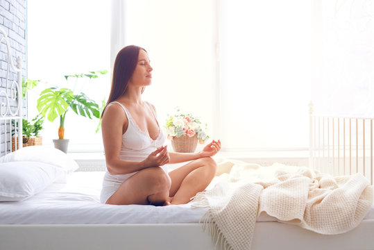 Concentrated pregnant woman meditating in bedroom