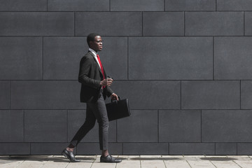 Tuinposter Fantasie Landschap Full-length portrait of handsome African American entrepreneur walking on pavement with gray block wall in background, dressed in black suit, holding leather bag and coffee cup during break in work