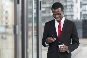 Indoor portrait of busy African chief executive officer pictured in afternoon, holding smartphone in hands and coffee cup, looking attentively at screen with satisfied happy smile while checking web