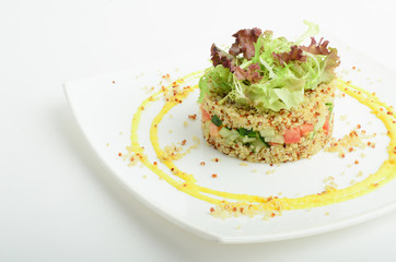 Salad with quinoa, cucumber and tomato decorated salad leaves and yellow sauce isolated on white background