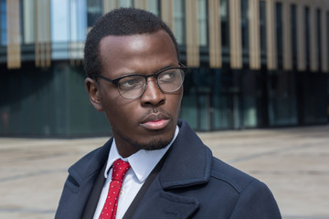 Horizontal headshot of dark-skinned African entrepreneur standing in street standing against high buildings in city center casting serious look through stylish spectacles feeling concentrated