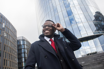 Street closeup of young handsome African American businessman walking alone in city center with skyscrapers in background, looking through eyeglasses to street with excited smile and satisfaction