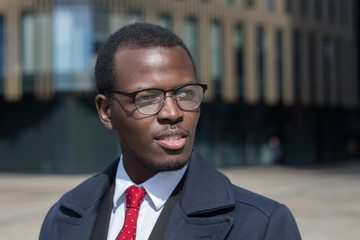 Urban portrait of African American businessman walking alone in city center dressed in dark coat and suit with red tie, looking to street with attention and hopeful smile seeking new ideas for work