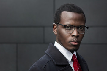 Urban portrait of handsome African male pictured against gray wall, wearing formal clothes and black-rimmed eyeglasses showing interested look while planning new activities for his business work