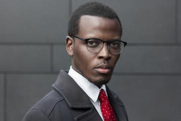 Horizontal headshot of African American entrepreneur standing isolated against dark grey wall, dressed in black coat, white shirt and red tie, looking concentrated and serious, thinking about plans