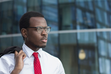 Horizontal image of dark-skinned African guy standing outdoors in white shirt with coat hanging on fingers, looking serious and tense as he is watching street in business city center during break