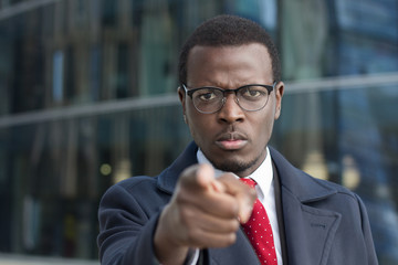 Horizontal headshot of alert african executive standing outdoors in business part of city drawing attention to user with forefinger as if emphasizing something important