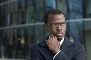 Horizontal headshot of young dark-skinned male standing in coat outdoors looking sideways with expression of suspicion and doubt while finding most effective way out of difficult situation in business