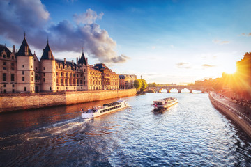 Dramatic sunset over Cite in Paris, France, with Conciergerie, Pont Neuf and river Seine. Colourful travel background. Romantic cityscape.