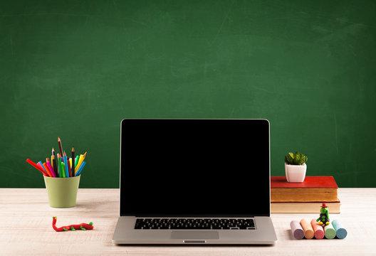 School items on desk with empty chalkboard
