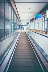 Modern long walkway of escalator moving forward at airport terminal.