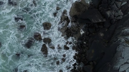 Wall Mural - Aerial view looking down at sea waves hitting black rocks