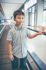 Happy asian child standing and smiling on electric speedwalk at modern airport.