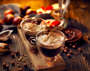 Hot chocolate with whipped cream, sprinkled with aromatic cinnamon in glass cups,  on a rustic wooden table