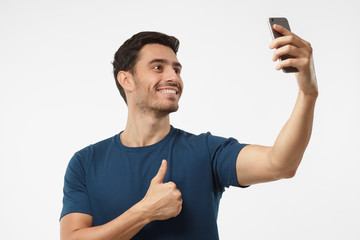 Photo of handsome male isolated on grey background, stretching arm with smartphone to take selfie picture to share it in social networks