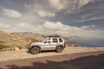 Road trip car in high mountains with lake view
