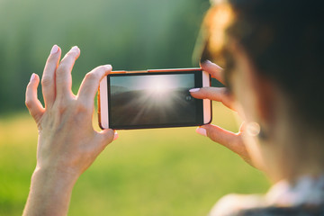 A woman is making a photo on a smartphone.