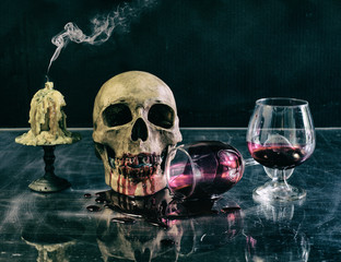 Skull with blood glass and candle in Halloween night