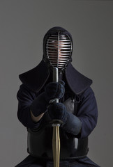 Portrait of man kendo fighter with shinai (bamboo sword) in traditional uniform.