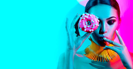 Foto op Canvas Beauty Fashion model woman posing in studio with donut in colorful bright lights