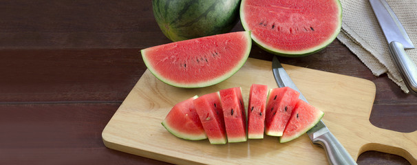 Watermelon slices on chopping board and knife all on wooden table, Adjustment size for banner, cover, header