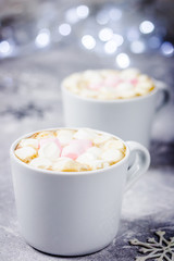 Hot chocolate winter christmas drink, lights, snowflakes. Selective focus, space for text, close up.