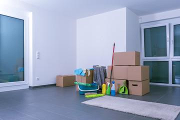 Helle, leere Luxuswohnung mit Kartons und Putzmittel auf schwarzem Fliesenboden
