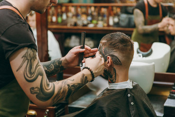 Close up shot of man getting trendy haircut at barber shop. Male hairstylist in tattoos serving client.