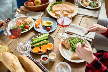 High angle closeup of festive dinner table with delicious food on it and people enjoying holiday celebration